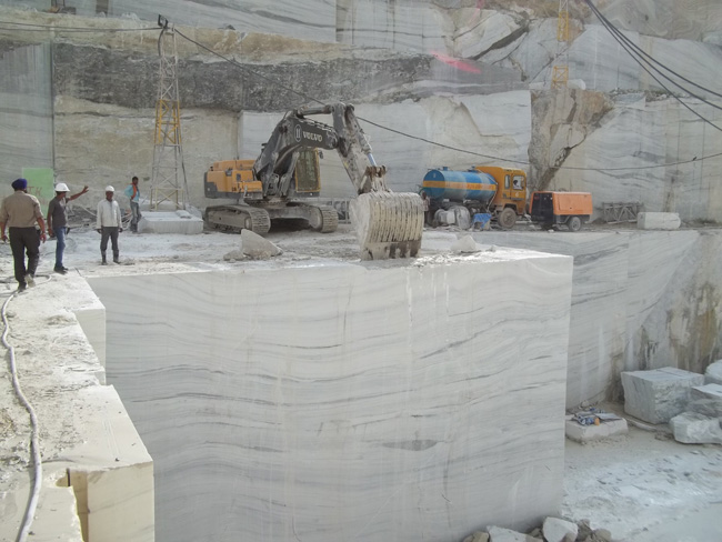 Volvo excavator being used by JK Natural Mables to push a large marble block away from the bench650.jpg