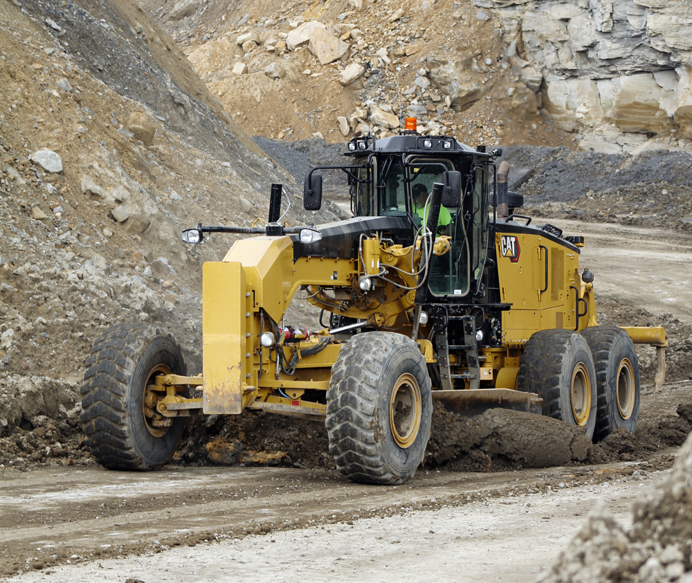 A motor grader driven by a trained operator is crucial in clearing and grading haul roads