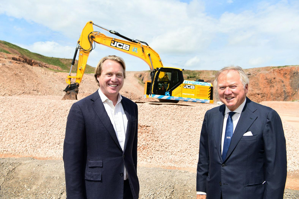 JCB chairman Lord Bamford (right) and his son Jo Bamford with the new 20-tonne JCB 220X excavator