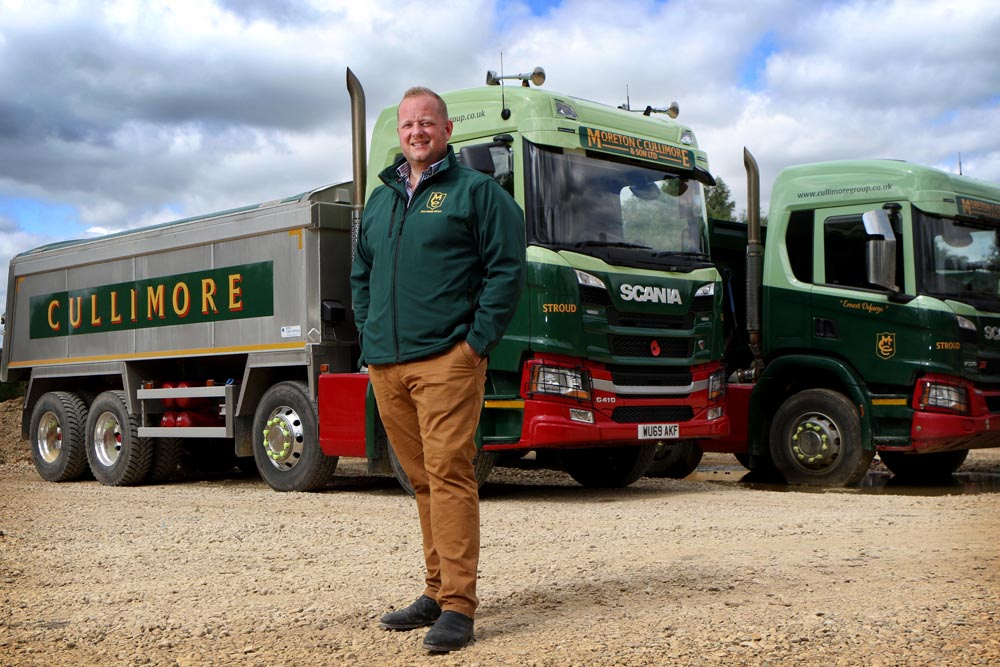 Moreton Cullimore in front of two of The Cullimore Group's haulage trucks
