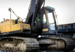 Excavator driving through mud